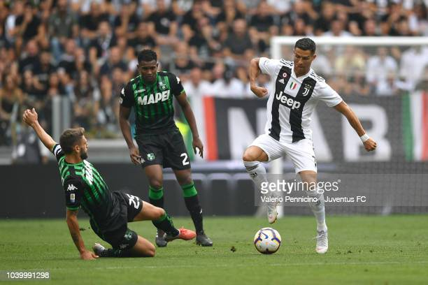 Cristiano Ronaldo of Juventus is tackled by Domenico Berardi of US Sassuolo during the serie A match between Juventus and US Sassuolo at Allianz...