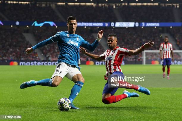 Cristiano Ronaldo of Juventus is tackled by Renan Lodi of Atletico Madrid during the UEFA Champions League group D match between Atletico Madrid and...