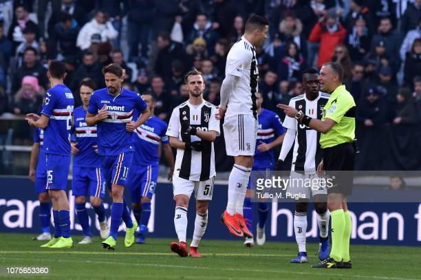 Cristiano Ronaldo of Juventus jumps in the air in front of referee Paolo Valeri as Fabio Quagliarella of Sampdoria celebrates after scoring a penalty...