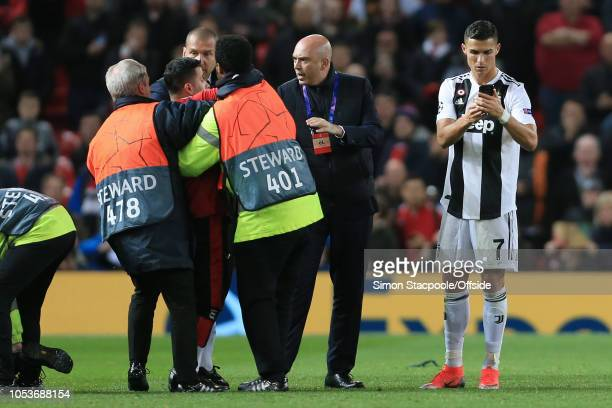Cristiano Ronaldo of Juventus looks at a mobile phone as he prepares to take a selfie with a pitch-invader fan being held back by stewards after the...