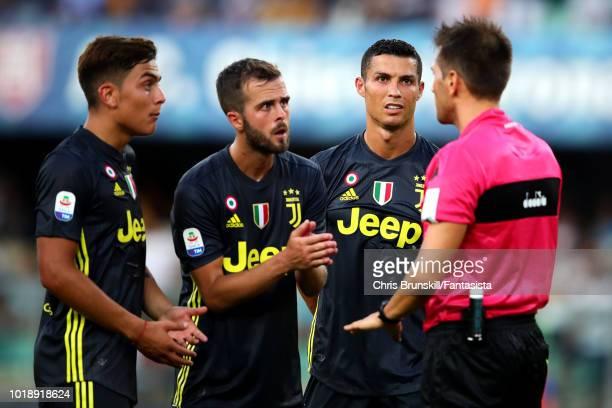 Cristiano Ronaldo of Juventus looks on as teammates Paulo Dybala and Miralem Pjanic complain to referee Fabrizio Pasqua during the Serie A match...
