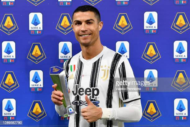 Cristiano Ronaldo of Juventus poses for a picture with his November 2020 MVP trophy prior to the Serie A match between Juventus and Torino FC at...