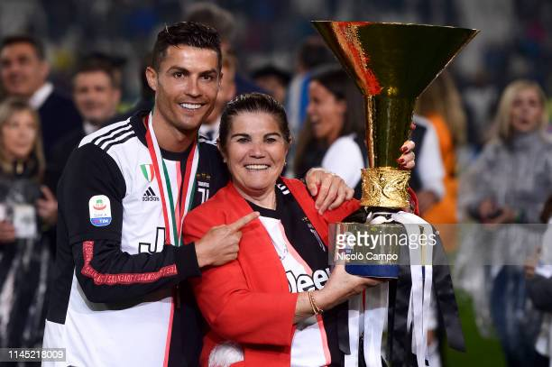 Cristiano Ronaldo of Juventus poses with the Serie A trophy alongside his mother Maria Dolores dos Santos Aveiro after winning the Serie A...