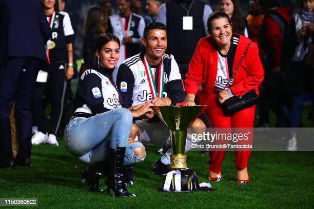Cristiano ROnaldo of Juventus poses with the Serie A trophy alongside his girlfriend Georgina Rodríguez and mother Maria Dolores dos Santos Aveiro...
