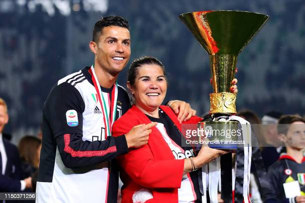 Cristiano Ronaldo of Juventus poses with the Serie A trophy alongside his mother Maria Dolores dos Santos Aveiro following the Serie A match between...