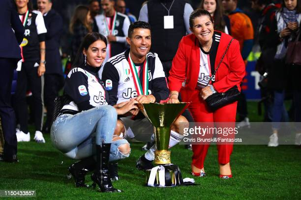 Cristiano Ronaldo of Juventus poses with the Serie A trophy alongside his girlfriend Georgina Rodríguez and mother Maria Dolores dos Santos Aveiro...