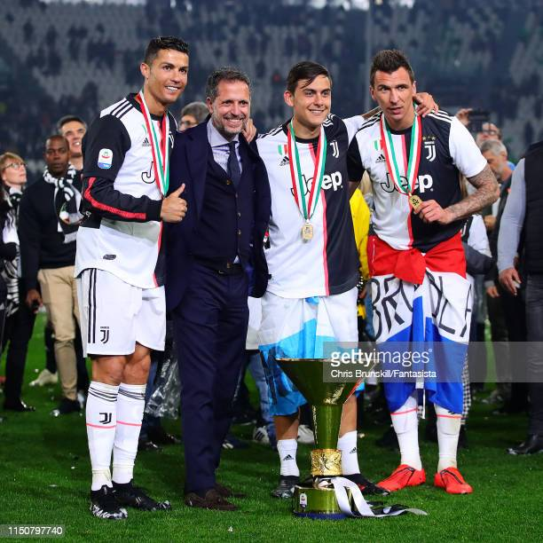 Cristiano Ronaldo of Juventus poses with the Serie A trophy alongside teammates Paulo Dybala and Mario Mandzukic following the Serie A match between...