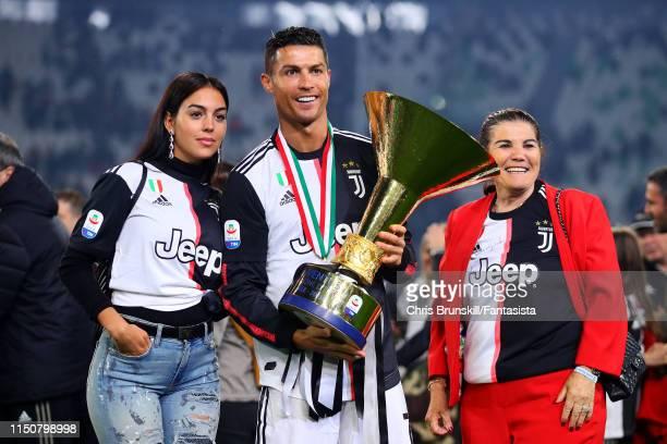 Cristiano Ronaldo of Juventus poses with the Serie A trophy alongside his girlfriend Georgina Rodriguez and mother Maria Dolores dos Santos Aveiro...