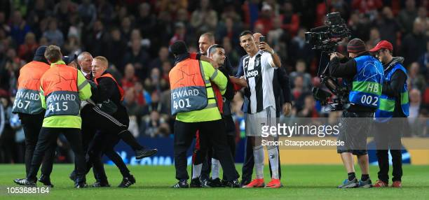 Cristiano Ronaldo of Juventus takes a selfie on a mobile phone for a pitch invader fan after the Group H match of the UEFA Champions League between...