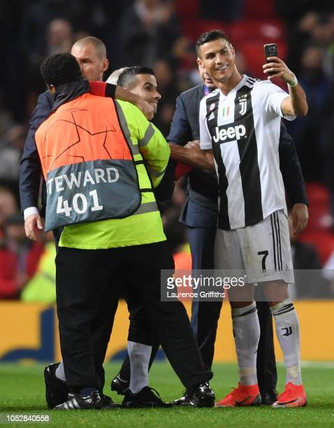 Cristiano Ronaldo of Juventus takes a selfie with a pitch invader after the Group H match of the UEFA Champions League between Manchester United and...