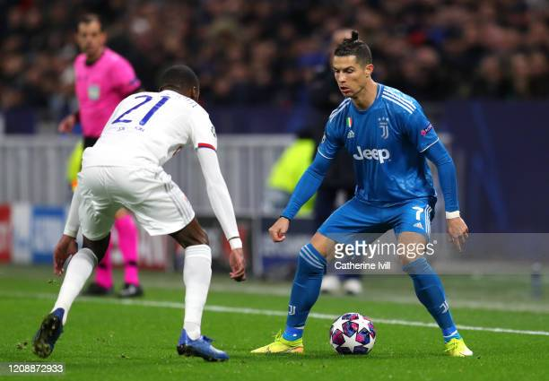 Cristiano Ronaldo of Juventus takes on Karl Toko Ekambi of Olympique Lyon during the UEFA Champions League round of 16 first leg match between...