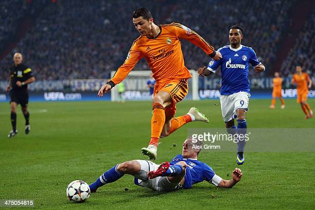 Cristiano Ronaldo of Madrid eludes Benedikt Hoewedes and KevinPrince Boateng of Schalke during the UEFA Champions League Round of 16 first leg match...
