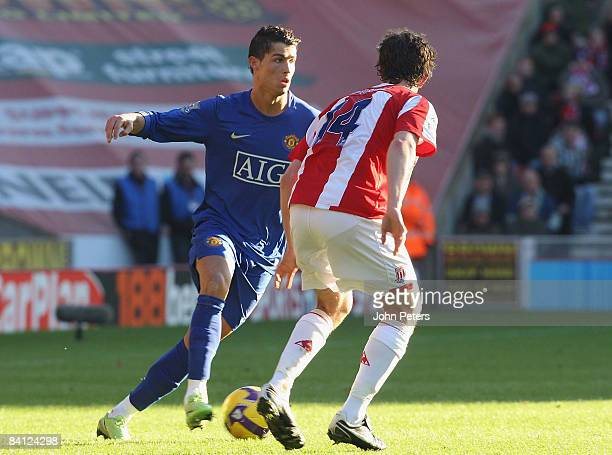 Cristiano Ronaldo of Manchester United clashes with Danny Pugh of Stoke City during the Barclays Premier League match between Stoke City and...