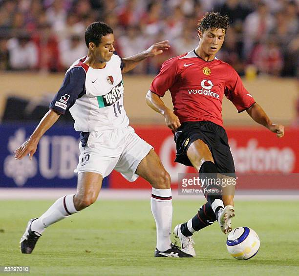 Cristiano Ronaldo of Manchester United clashes with Fernando of Kashima Antlers during the preseason friendly match between Kashima Antlers and...