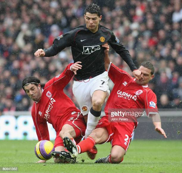 Cristiano Ronaldo of Manchester United clashes with Julio Arca and Luke Young of Middlesbrough during the Barclays FA Premier League match between...