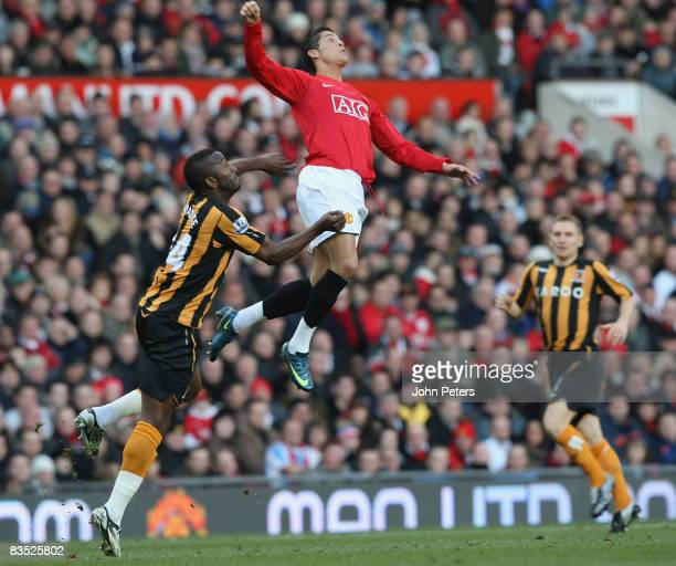 Cristiano Ronaldo of Manchester United clashes with Kamil Zayatte of Hull City during the Barclays Premier League match between Manchester United and...
