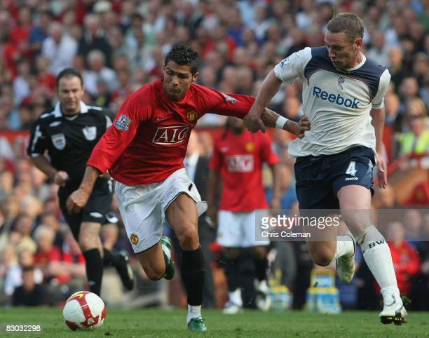 Cristiano Ronaldo of Manchester United clashes with Kevin Nolan of Bolton Wanderers during the FA Premier League match between Manchester United and...