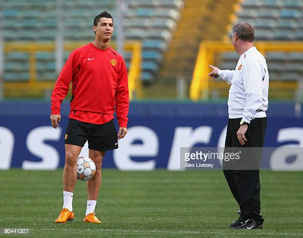 Cristiano Ronaldo of Manchester United controls the ball as he talks with Sir Alex Ferguson during the Manchester United training session held at the...