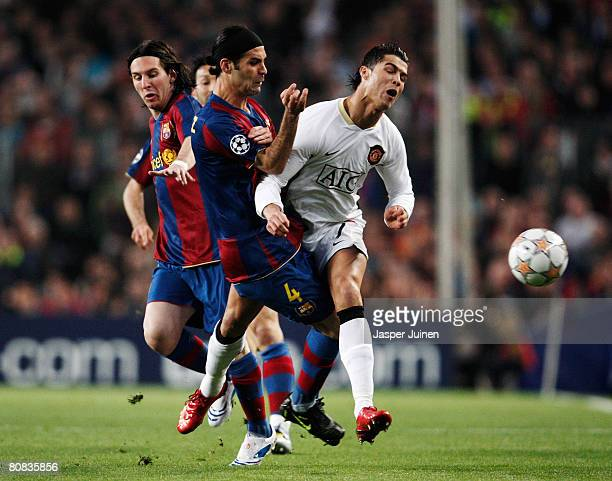 Cristiano Ronaldo of Manchester United is challenged by Rafael Marquez and Lionel Messi of Barcelona during the UEFA Champions League SemiFinal first...