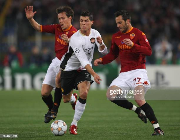 Cristiano Ronaldo of Manchester United is challenged by Rodrigo Taddei and Marco Cassetti of AS Roma during the UEFA Champions League Quarter Final...