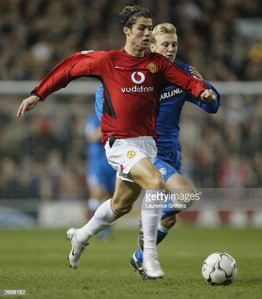 Cristiano Ronaldo of Manchester United is chased by Stephen Hughes of Rangers during the UEFA Champions League match between Manchester United and...