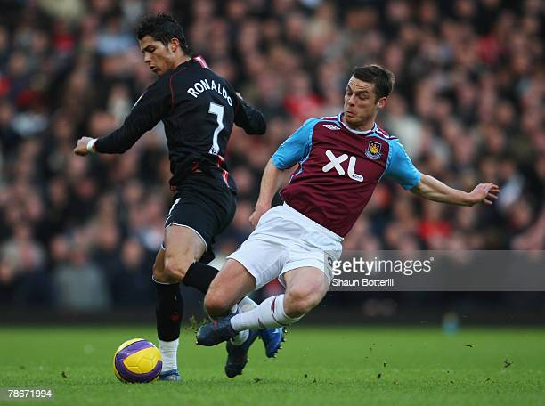 Cristiano Ronaldo of Manchester United is tackled by Scott Parker of West Ham United during the Barclays Premier League match between West Ham United...