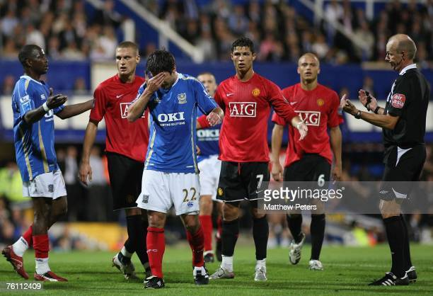 Cristiano Ronaldo of Manchester United looks surprised at the reaction of Richard Hughes of Portsmouth after a clash for which Ronaldo was sent off...