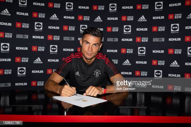 Cristiano Ronaldo of Manchester United poses after signing his contract with the club at Carrington Training Ground on September 08, 2021 in...