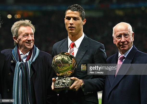 Cristiano Ronaldo of Manchester United receives the Ballon d'or as the European Footballer of the Year flanked by previous winners Denis Law and...
