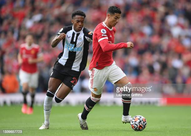 Cristiano Ronaldo of Manchester United runs with the ball whilst under pressure from Joe Willock of Newcastle United during the Premier League match...