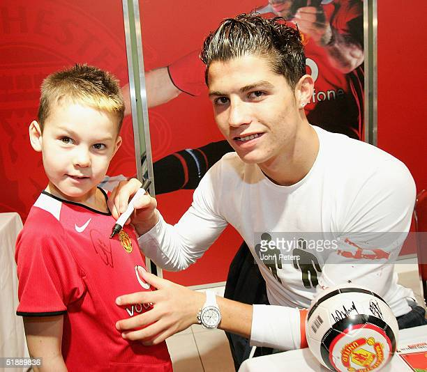 Cristiano Ronaldo of Manchester United signs a young fan's shirt during a signing session at Manchester United's Megastore at Old Trafford on...
