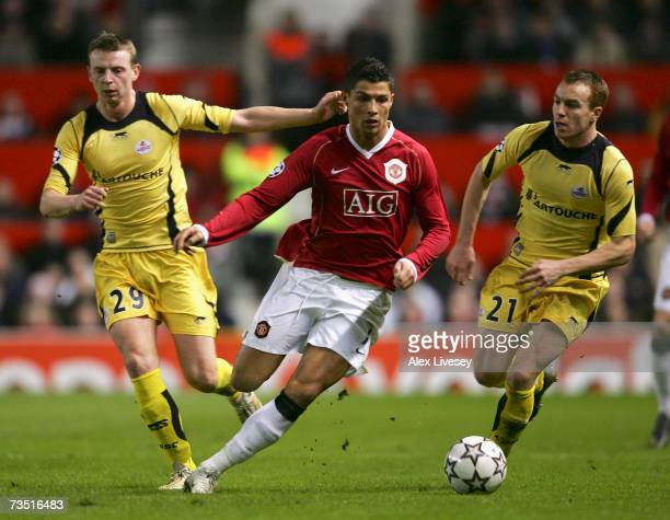 Cristiano Ronaldo of Manchester United surges past Stephane Dumont and Matthieu Chalme of Lille during the UEFA Champions League round of sixteen,...
