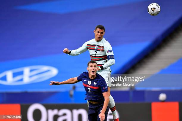 Cristiano Ronaldo of Portugal and Benjamin Pavard of France jump for the ball during the UEFA Nations League group stage match between France and...