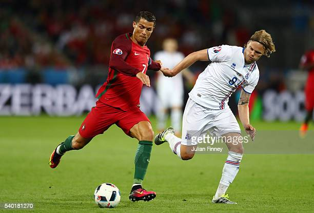 Cristiano Ronaldo of Portugal and Birkir Bjarnason of Iceland compete for the ball during the UEFA EURO 2016 Group F match between Portugal and...