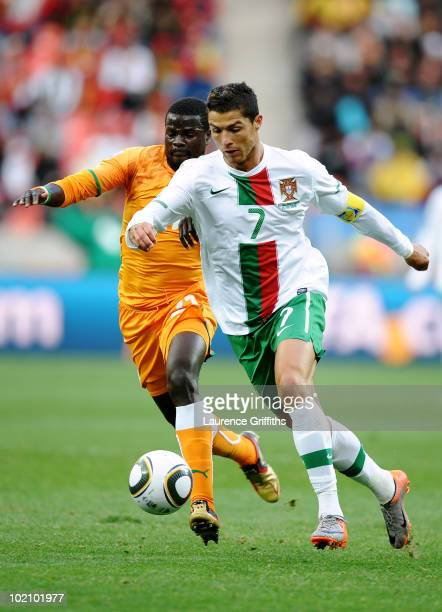 Cristiano Ronaldo of Portugal and Emmanuel Eboue of Ivory Coast battle for the ball during the 2010 FIFA World Cup South Africa Group G match between...
