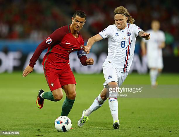 Cristiano Ronaldo of Portugal battles with Birkir Bjarnason of Iceland during the UEFA EURO 2016 Group F match between Portugal and Iceland at Stade...