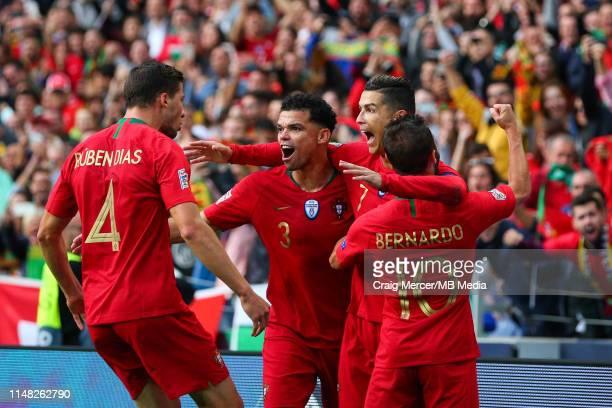 Cristiano Ronaldo of Portugal celebrates scoring the opening goal with team mates Bernardo Silva, Pepe and Ruben Dias during the UEFA Nations League...
