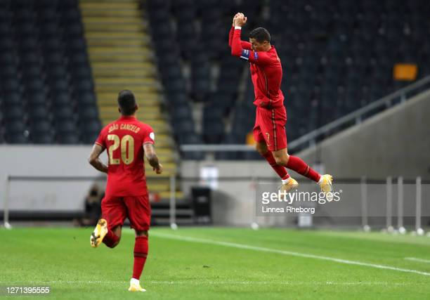 Cristiano Ronaldo of Portugal celebrates with teammate Joao Cancelo after scoring his team's first goal during the UEFA Nations League group stage...