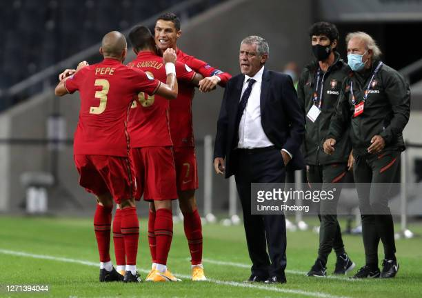 Cristiano Ronaldo of Portugal celebrates with teammates Joao Cancelo and Pepe of Portugal after scoring his team's first goal during the UEFA Nations...