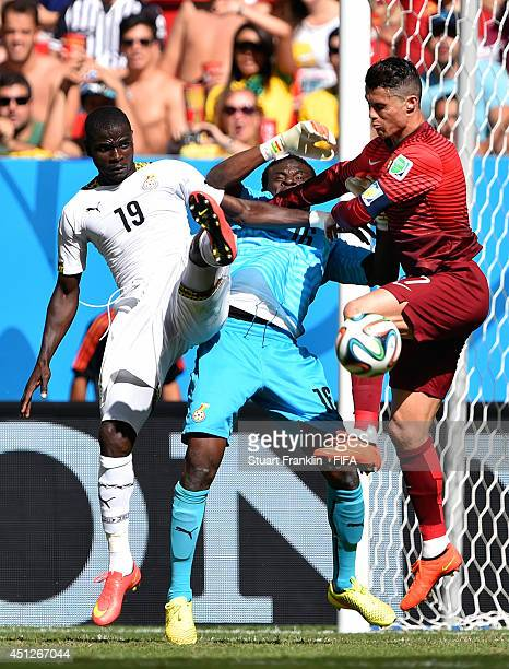 Cristiano Ronaldo of Portugal challenges Jonathan Mensah and Fatawu Dauda of Ghana during the 2014 FIFA World Cup Brazil Group G match between...