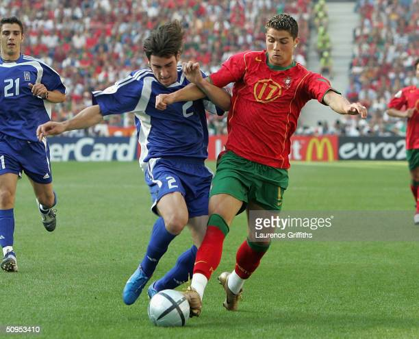 Cristiano Ronaldo of Portugal clashes with Georgios Seitardis of Greece during the Portugal v Greece Group A opening match the 2004 UEFA European...