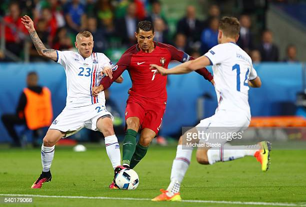 Cristiano Ronaldo of Portugal competes for the ball against Ari Skulason and Kari Arnason of Iceland during the UEFA EURO 2016 Group F match between...