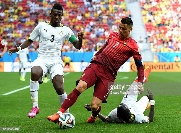 Cristiano Ronaldo of Portugal competes for the ball against Asamoah Gyan and Mohammed Rabiu of Ghana during the 2014 FIFA World Cup Brazil Group G...