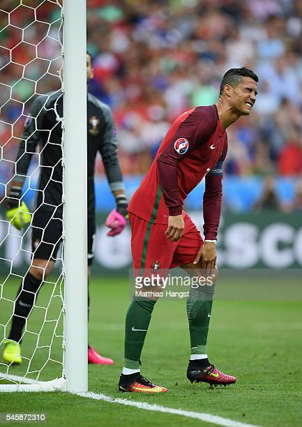 Cristiano Ronaldo of Portugal holds his knee during the UEFA EURO 2016 Final match between Portugal and France at Stade de France on July 10 2016 in...