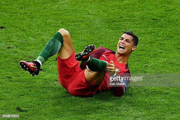 Cristiano Ronaldo of Portugal holds his knee during the UEFA EURO 2016 Final match between Portugal and France at Stade de France on July 10, 2016 in...