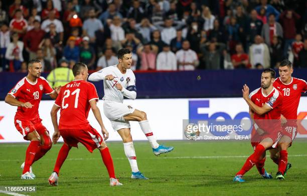 Cristiano Ronaldo of Portugal in action against Luka Milivojevic and Nemanja Matic of Serbia during the UEFA Euro 2020 qualifier between Serbia and...