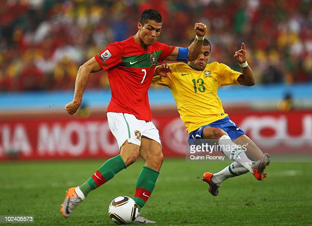 Cristiano Ronaldo of Portugal is challenged by Dani Alves of Brazil during the 2010 FIFA World Cup South Africa Group G match between Portugal and...