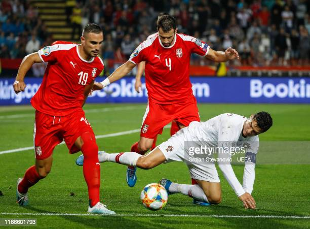 Cristiano Ronaldo of Portugal is challenged by Luka Milivojevic and Nikola Maksimovic of Serbia during the UEFA Euro 2020 qualifier between Serbia...
