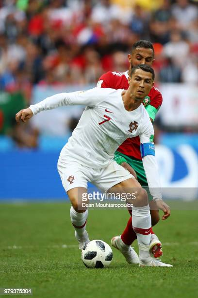 Cristiano Ronaldo of Portugal is challenged by Mehdi Benatia of Morocco during the 2018 FIFA World Cup Russia group B match between Portugal and...