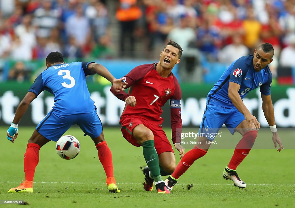 Cristiano Ronaldo (C) of Portugal is challenged by Patrice Evra (L) and Dimitri Payet (R) of France during the UEFA EURO 2016 Final match between Portugal and France at Stade de France on July 10, 2016 in Paris, France.